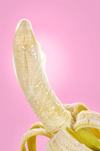Banana with condom protection Banana Condom Protection Contraception Pink Color Pink Background Close-up Banana Peel
