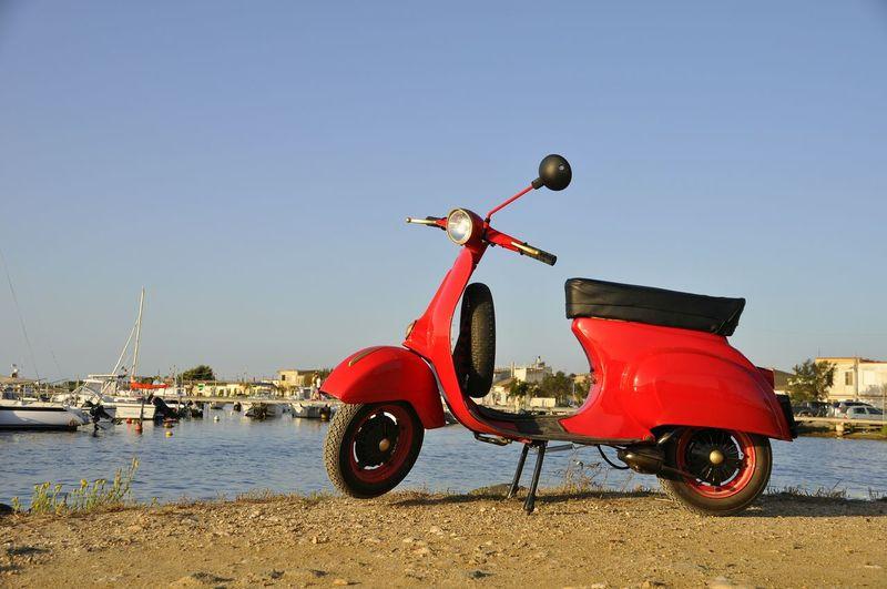Red toy car on beach against clear sky