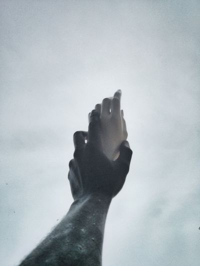 Low angle view of hands against sky