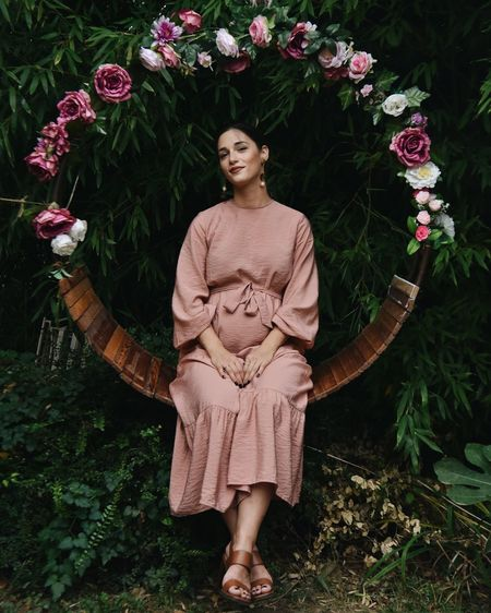 Portrait of woman standing on flowering plants
