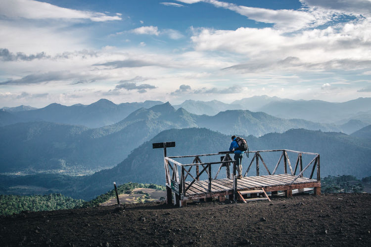 Man standing at observation point against mountains