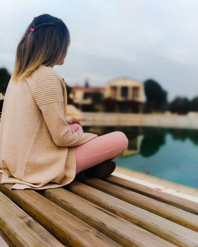Side view of girl sitting by swimming pool