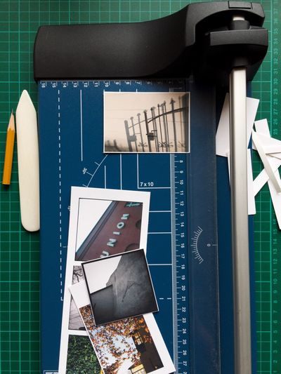 Directly above shot of photographs and measuring instrument on table