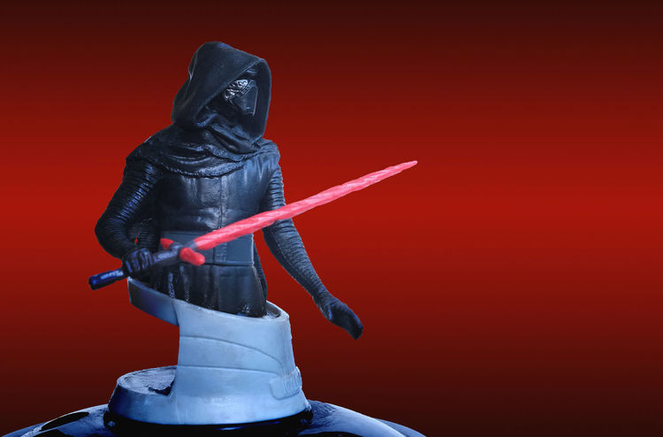 Trang Thailand - DEC 06, 2017: Kylo Ren of theatre bust series figure collection on red scene from star wars the last jedi movie. Box office greeting concept. Figure Jedi Kylo Ren Leader Light MOVIE Master Star Wars Black Character Cinema Dark Side Helmet Hood Lightsaber Mask Red Background Saber Sculpture Side View Skywalker Space Statue Toy War