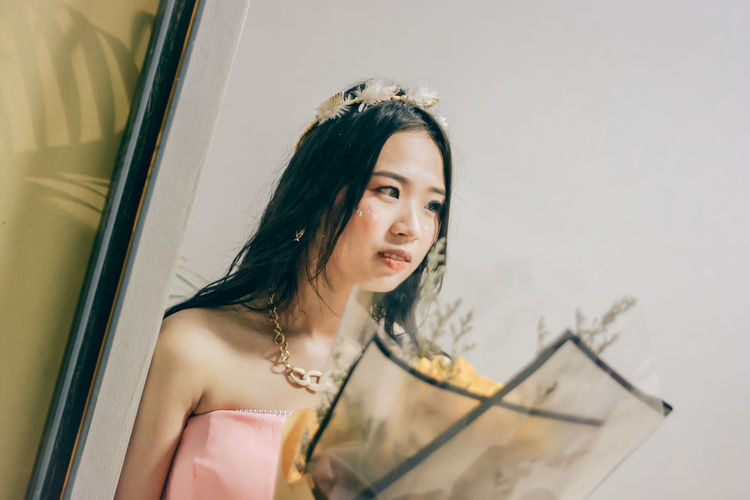 Reflection of young woman with bouquet seen in mirror