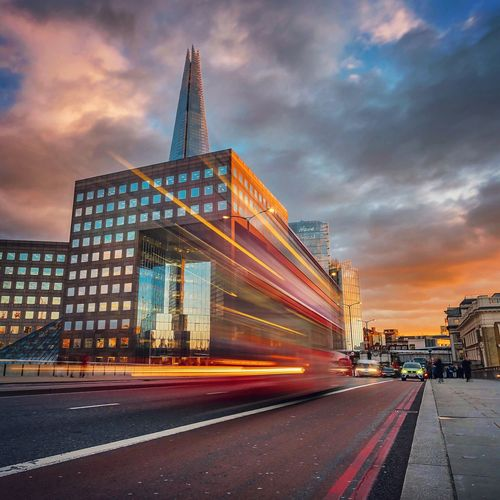 Light Trails On Road By The Shard Against Cloudy Sky At Sunset