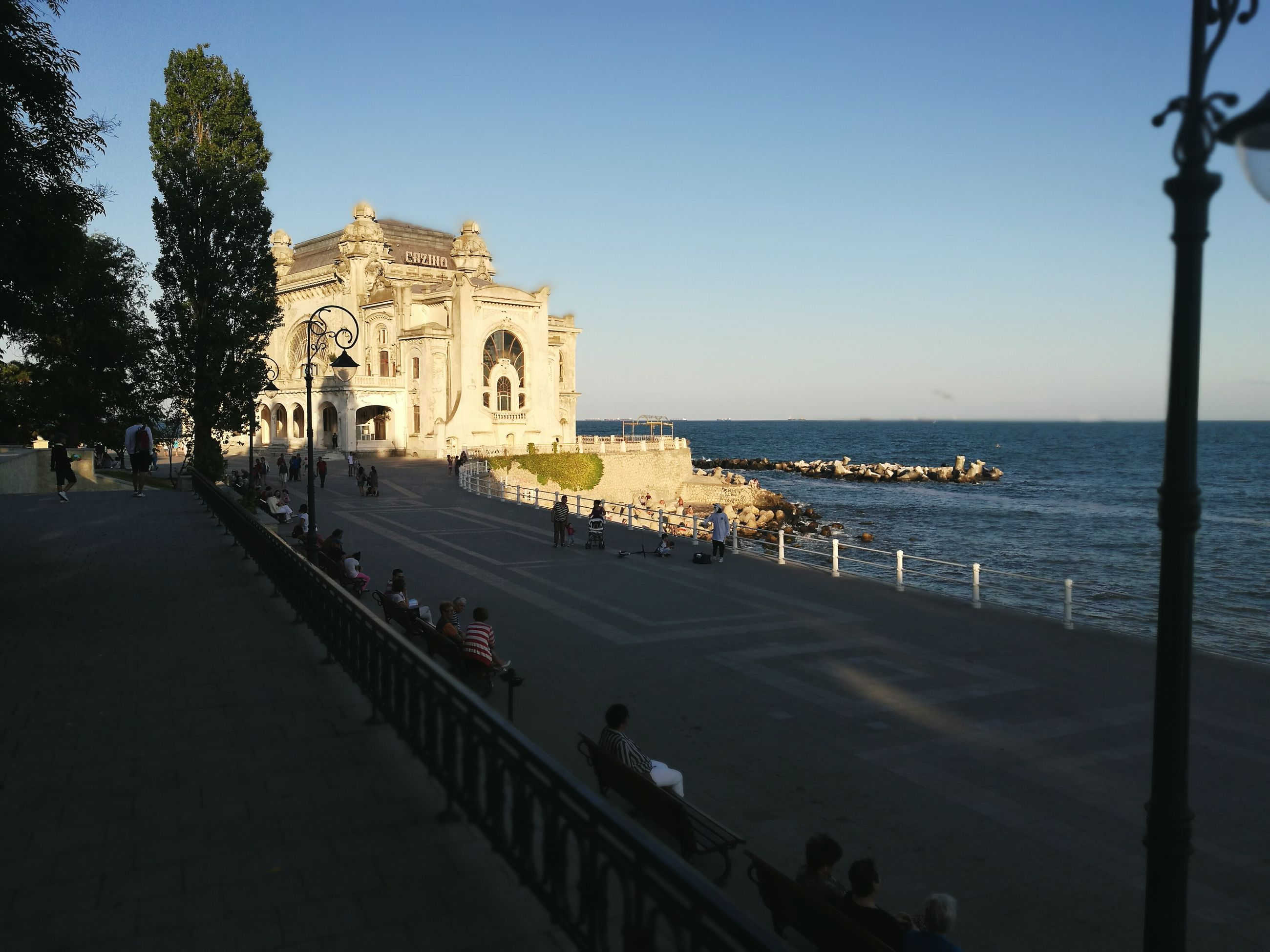 architecture, built structure, water, sea, clear sky, building exterior, horizon over water, large group of people, spirituality, street light, tourism, travel destinations, tourist, place of worship, vacations, tranquility, outdoors, scenics, person, day, tranquil scene, city life, weekend activities
