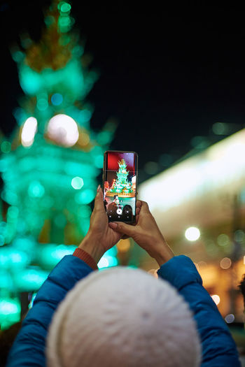Rear view of woman photographing with smart phone at night