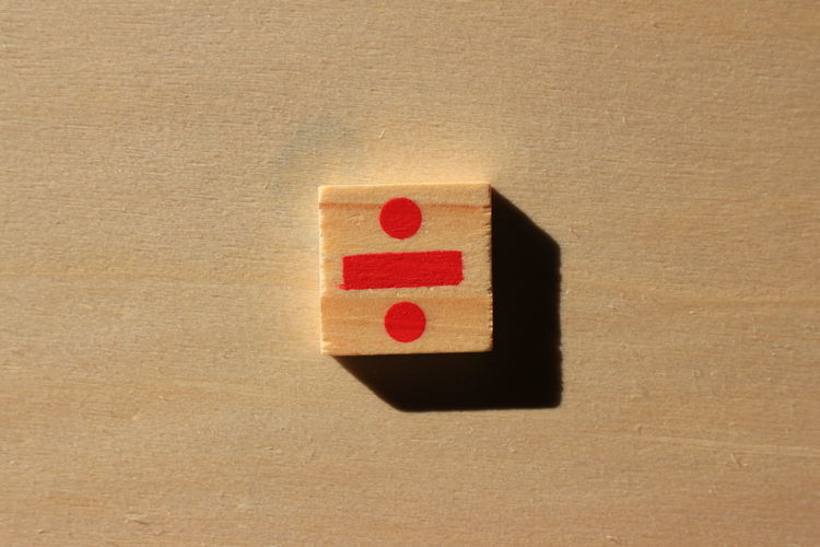 Close-up of division sign on wood