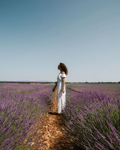 Woman standing in a lavender field against clear sky