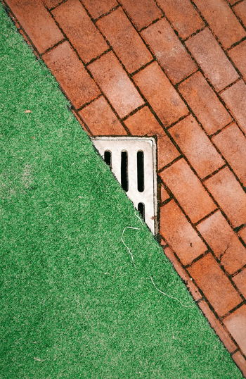 View Of A Drain In Between Brick And Grass