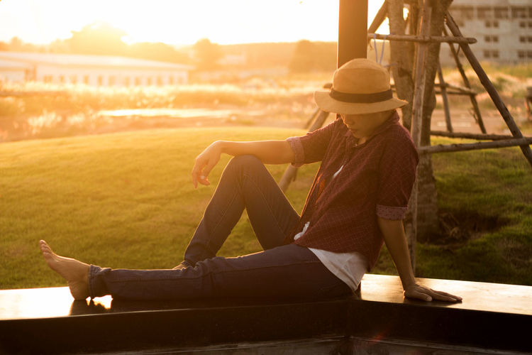 Side View Of Woman Sitting On Railing During Sunset