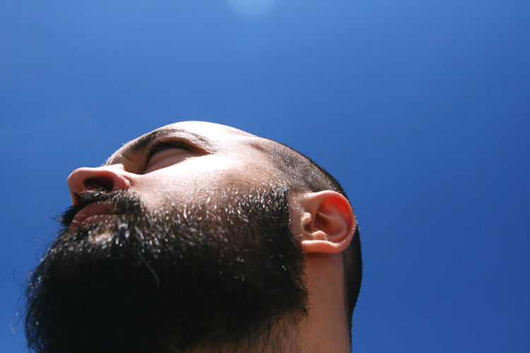 Close-up portrait of man against blue sky