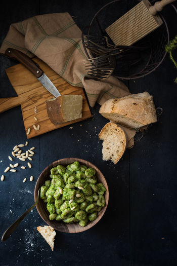 bowl with pesto gnocchi Bowl Bread Condiment Cutting Board Dumpling  Food Gnocchi Green Color Homemade Italian Food Knife Knife And Fork Light And Shade Mediterranean Diet No People Pecorino Cheese Pesto Pesto Alla Genovese Pine Nuts Sauce Savory Set The Table Tradition Whole Wood