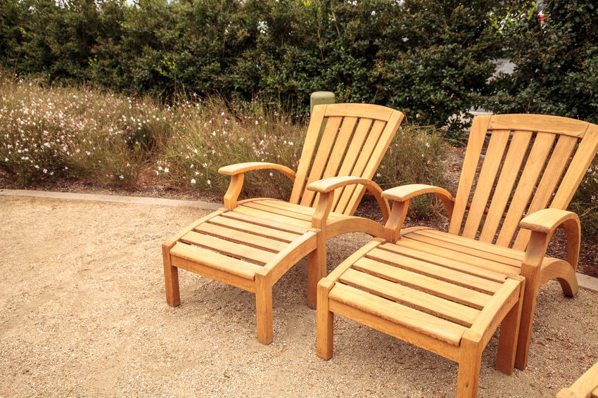 Wood patio lounge chairs in the backyard with green grass in the summer. Adirondack Chairs Backyard Relaxing Tranquility Furniture Lounge Chairs Patio Furniture Wood Chairs