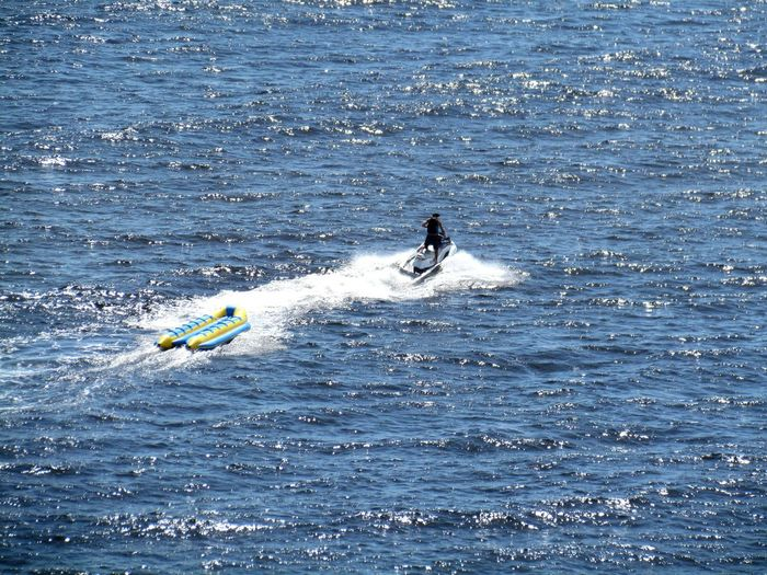 A man on a jet ski, pulling an inflatable banana boat. Banana Boat Jet Ski Adventure Beauty In Nature Day Extreme Sports Jet Skiing Leisure Activity Lifestyles Men Motion Nature Nautical Vessel Ocean One Person Outdoors People Real People Sea Skill  Sport Surfing Water Waterfront Wave