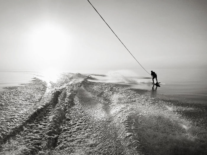 Silhouette man wakeboarding on sea against sky