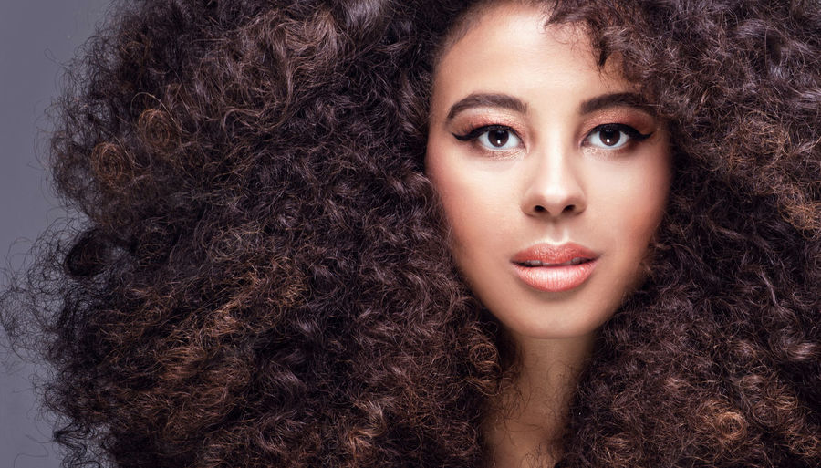 Close-up portrait of woman with curly hair against gray background