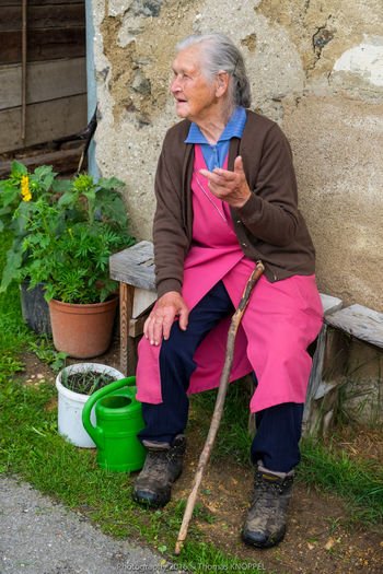 old woman 6 Alpine Casual Clothing Color Portrait Country Life Day Expression Face Grey Hair Life Experience Mature Adult Old Woman Portrait Outdoors Person Sitting On A Bench Talking Talking With Hand Telling Stories