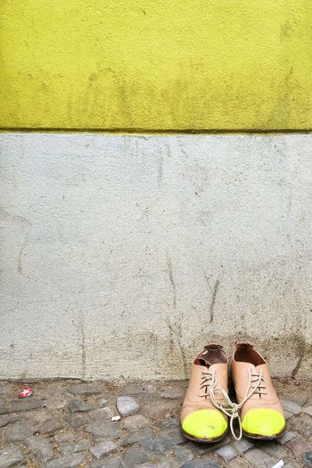 Shoes on street against wall