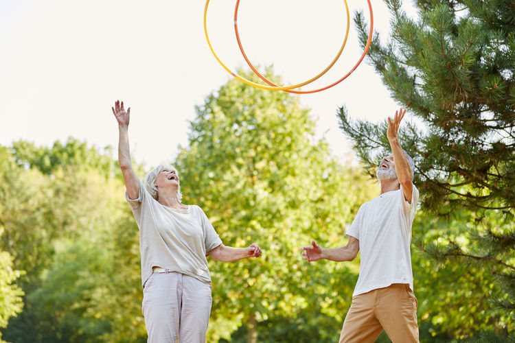 Senior Couple Playing With Plastic Hoops At Park
