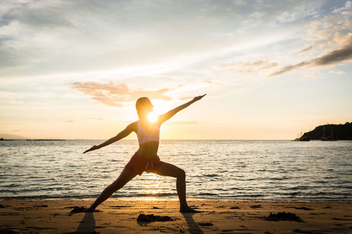 Woman on a tropical beach practicing yoga at sunset Woman Backlit Balance Beach Exercising Girl One Person Outdoors Real People Sea Sky Sunset Tranquil Scene Tranquility Warrior Pose Water Yoga