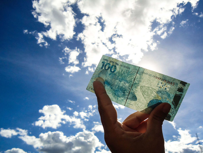 Cropped holding paper currency against sky