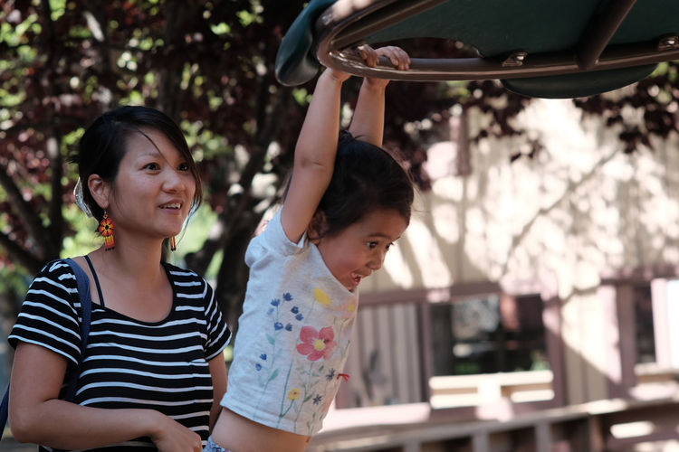Woman Looking At Daughter Hanging On Play Equipment At Playground