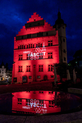 Red building against sky at night