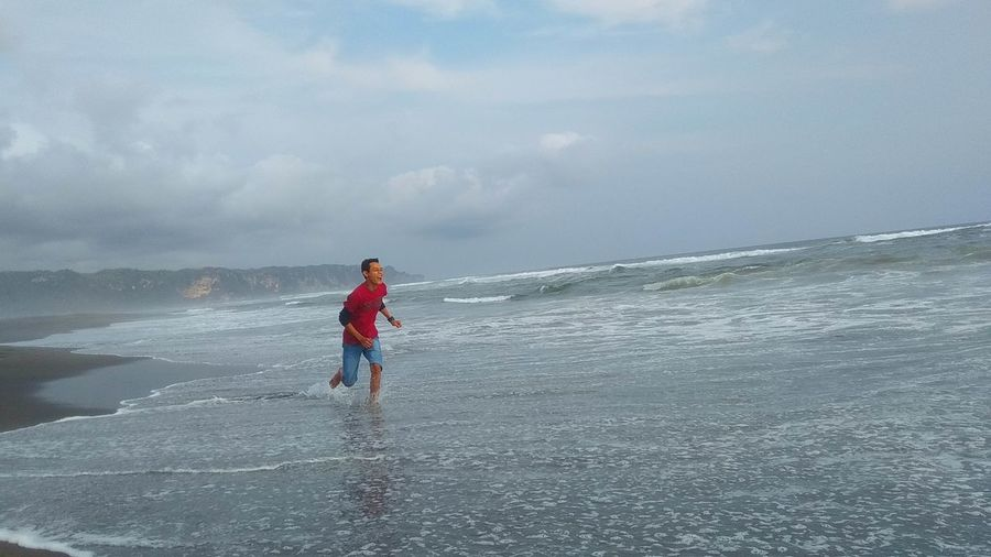 Man running in sea against sky
