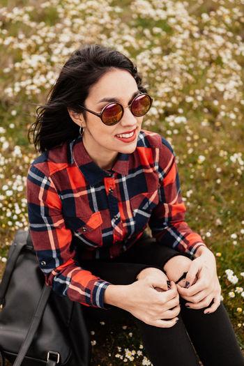 Young woman wearing sunglasses sitting on land