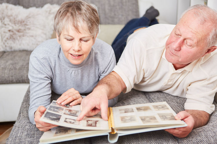Senior Couple Looking At Photographs On Bed At Home