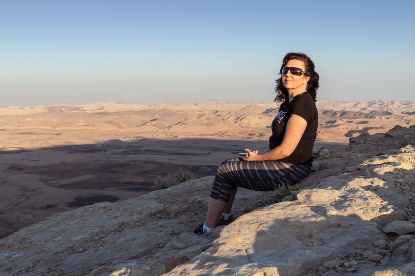 A alone young girl sits on the mountain cliff at sunset on the Judean desert in Israel Sunlight Background Beautiful Woman Beauty Cute Emotional Hairstyle Israel Judean Desert Leisure Activity Lifestyles Mountain Cliff Nature One Person Park person Relax Rock Scenics - Nature Sitting Sky Smile Sunset Women Young Adult