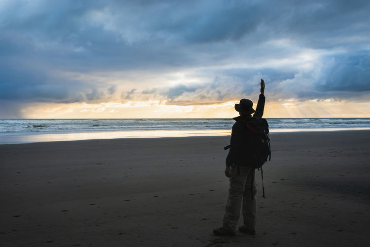 Rear view of silhouette person standing on beach against sky during sunset