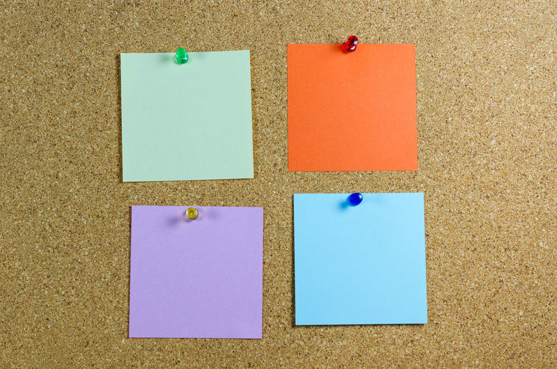Close-up of multi colored adhesive note on wall
