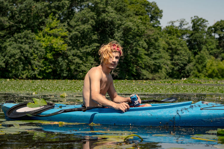 Kayaking on a Lake in Summer Beer Adventure Day Holiday Kayak Lake Leisure Activity Lifestyles Men Nature One Person Outdoors Plant Real People Shirtless Summer Three Quarter Length Tree Trip Vacations Water Young Adult The Great Outdoors - 2018 EyeEm Awards
