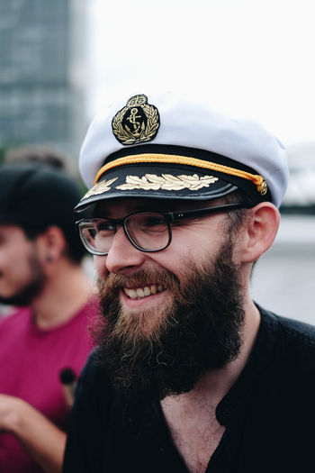 Smiling bearded man wearing eyeglasses and cap in city