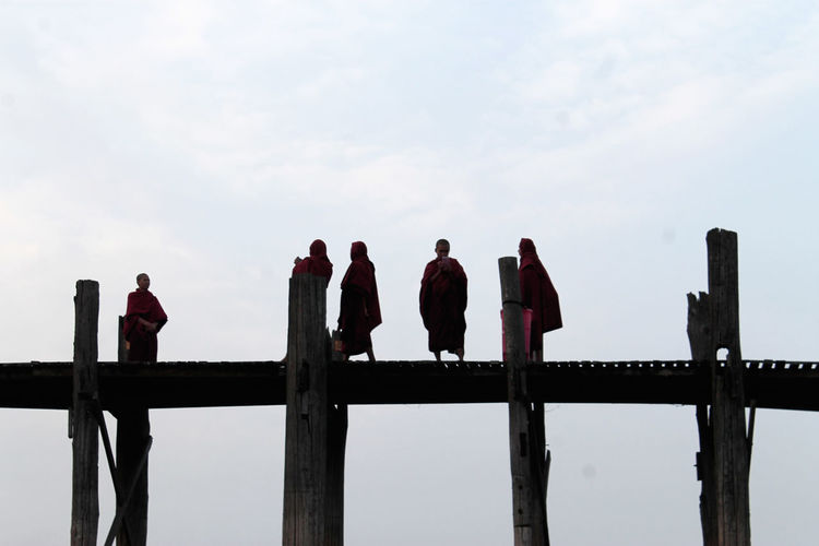U-BEIN BRIDGE/AMARAPURA, MYANMAR JAN 22, 2016: Silhuettes of buddhist monks wrapped on their daily walk across the bridge just before sunrise. Adult Amarapura Bridge Buddhism Buddhist Day Dusk Mandala Men Monks Myanmar Outdoors People Real People Religion Religious  S Silhuette Sky Togetherness Tradition Travel Destinations U-bein Bridge,Myanmar Walking Wooden An Eye For Travel