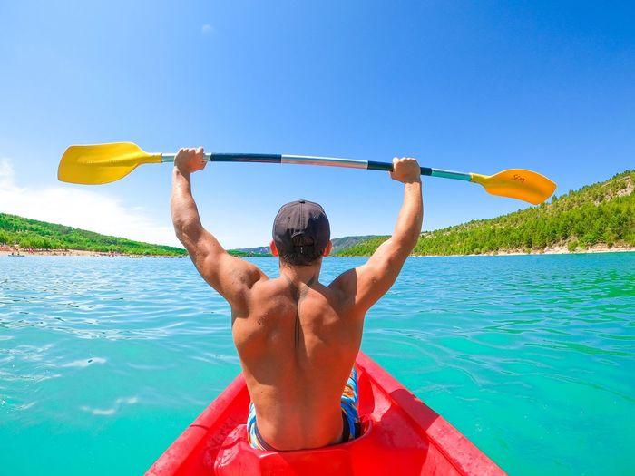 Rear view of shirtless man holding blue sea against sky