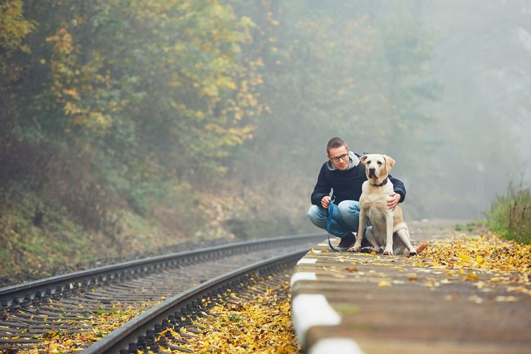 Young Man With Dog Crouching By Railroad Track