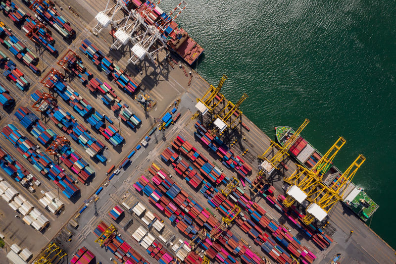 Container ship loading and unloading in sea port, aerial view of business logistic import