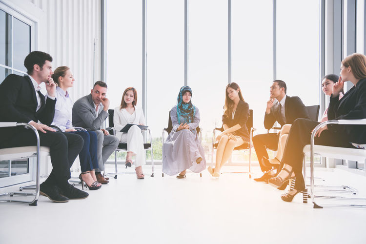 Colleagues discussing while sitting on chairs in office