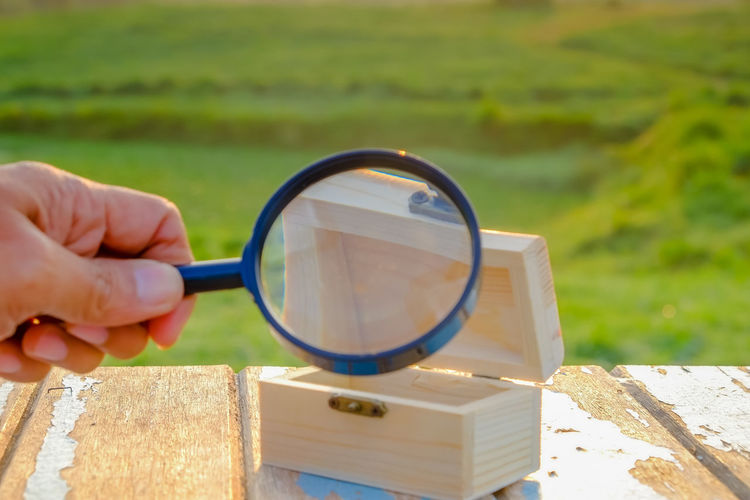 Cropped image of hand holding magnifying glass over wooden box on table