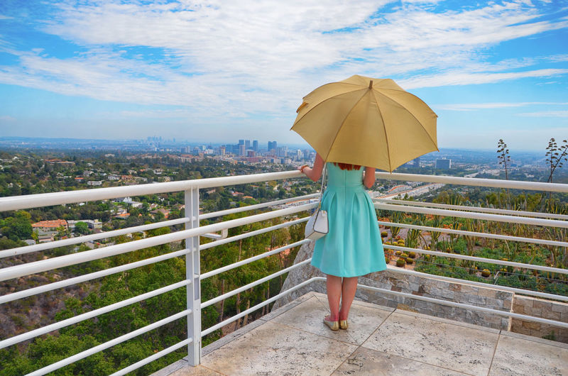 Rear view of woman with umbrella standing on railing