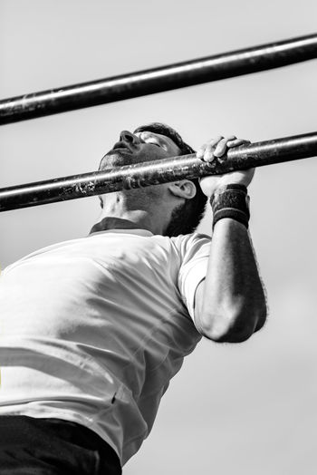 Male Doing Pull Ups On Cross Competition Fitness Cross Training Cross Fit Training Workout Athlete Muscular Competitive Sport Active Exercising Exercise Equipment Black White Black And White Lifestyle Young Attractive Outdoors Man Male Pull Ups Day Sky
