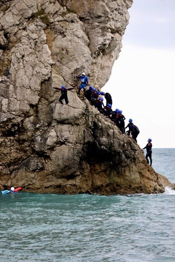 People climbing on rock formation over sea