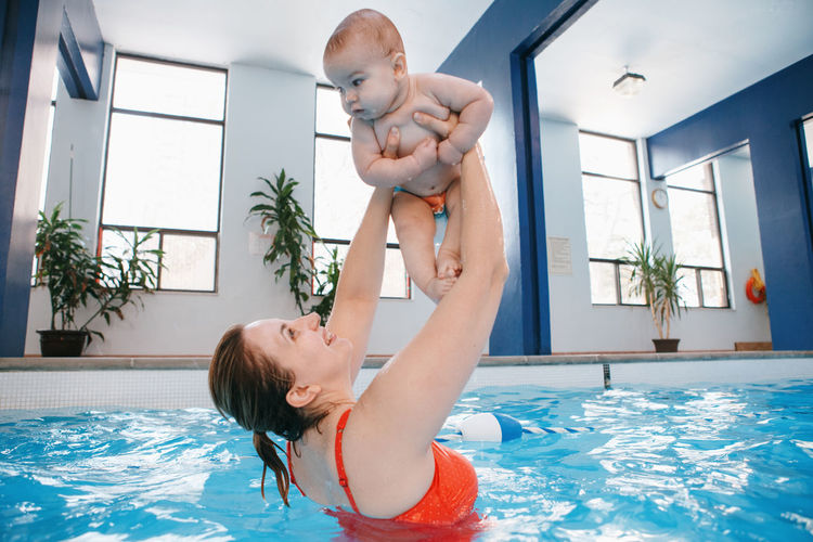 Woman holding baby boy in swimming pool