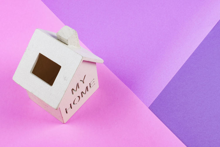 miniature wooden house on desk over colorful background Pink Color Indoors  Close-up No People Communication Text Number Wall - Building Feature Time Copy Space Clock Still Life Paper Technology Western Script Creativity Wall Architecture Heart Shape Single Object Minute Hand