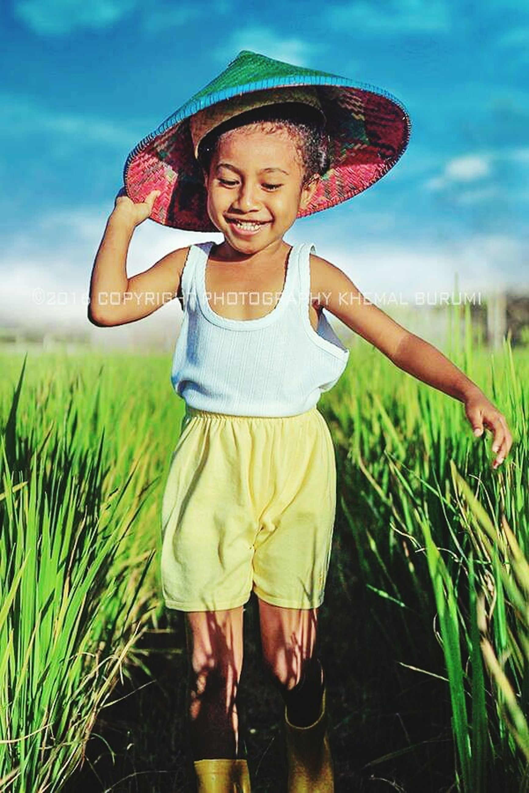 child, childhood, smiling, happiness, plant, hat, field, grass, one person, land, clothing, front view, girls, looking at camera, portrait, standing, casual clothing, nature, three quarter length, innocence, hair, outdoors