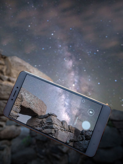 Close-up of mobile phone against sky at night